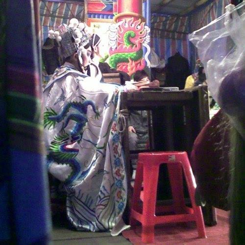 Taipei: The biggest event of Small New Year is the Taiwan traditional folklore culture called 布袋戯・歌仔戯.I taken the photos of 歌仔戯 in the backstage side, not front. (photo: Jan 17, 2013)台北:小正月の歌仔戯小正月の最大の行事は布袋戯・歌仔戯をはじめとした民俗演劇なのが台湾。布袋戯は人形芝居、歌仔戯は台湾オペラ。台湾土着の民俗ですから、台湾語で演じられます。今年も私の住む路地裏で執り行なわれました。夕方になると太鼓と銅鑼が部屋まで聞こえてきます。食事に出かける際に写真に収めることにしました。しかし毎回表の舞台を撮ってもどうということないので、今年は横から覗き込んでみます。右側が舞台表。二人の演者が舞っているんですが見えません。それではと後ろでドンと構えているオネーサンのスナップです。カメラを構えていると、舞台を出入りするオネーサンたちが私のほうをギョロッと見ていきます。ハイ、ゴメンなさいな。三年前の記事はこちら。 (via [台北] 路上の演劇 - 歌仔戯)