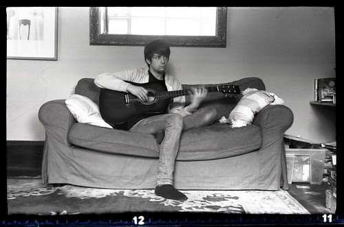 playing the blue guitar on the red sofa in black and white by pho-Tony