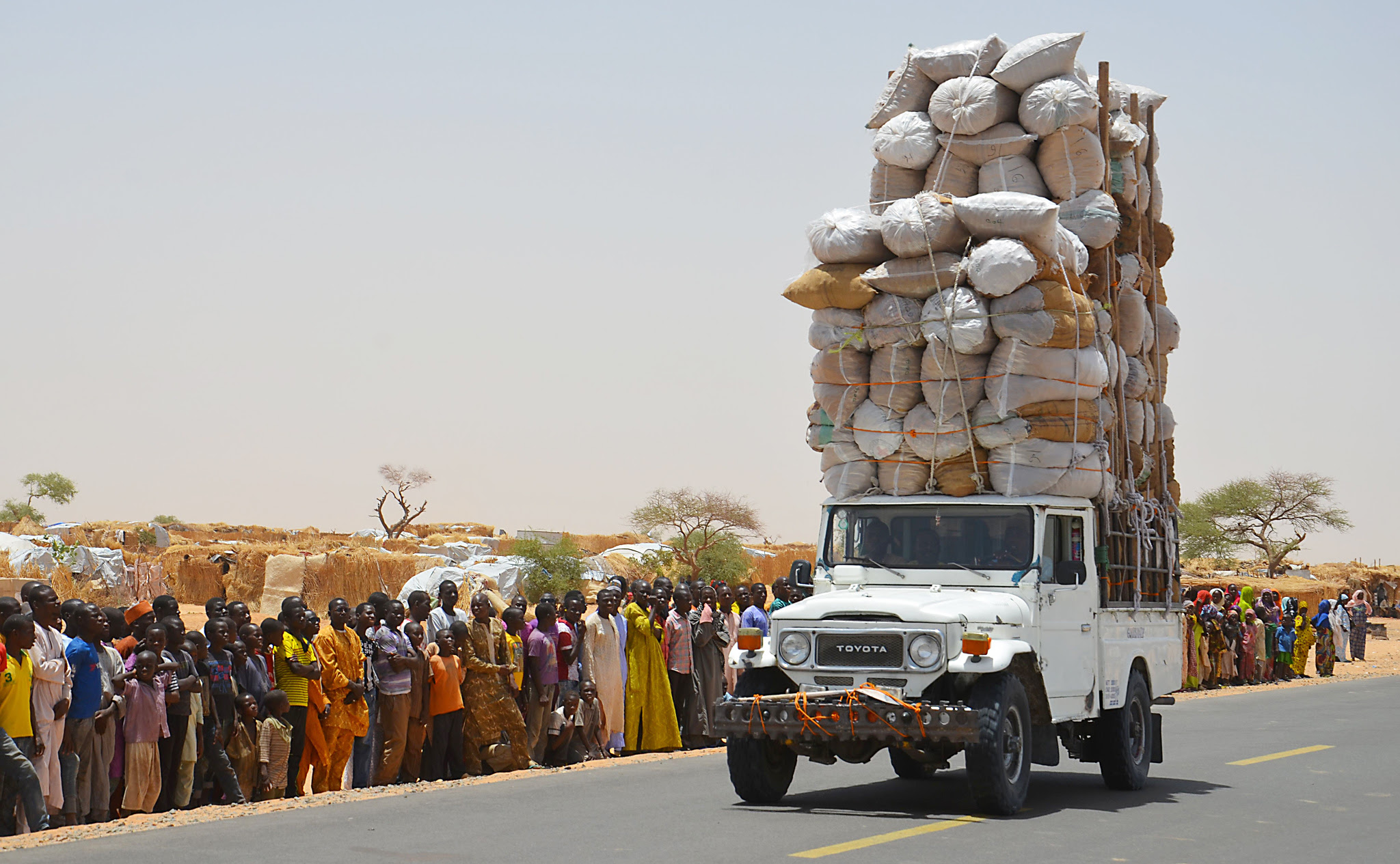 "TOPSHOT - An overloaded car travels through the Assaga refugee camp in Diffa on May 17, 2016, close to the Niger-Nigeria border.  Chief of Humanitarian Operations of the UN, Stephen O'Brien, vowed on May 17 to raise funds at the next World Humanitarian Summit for ""significant"" help to the more than 240,000 refugees displaced by Boko Haram in camps in south-east Niger. / AFP PHOTO / BOUREIMA HAMABOUREIMA HAMA/AFP/Getty Images"