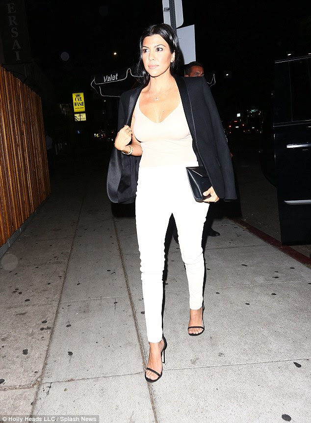 Figure envy! The reality star paired the style with form-fitting white trousers, slinky black stilettos and a sharp black blazer, which she draped coolly over her shoulders