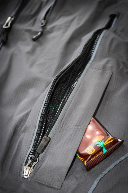 A closer shot of the vents in the Refuge Jacket, along with the side hand warmer pockets. The chest pocket zipper can be seen in the background. There is ample storage in this shell.