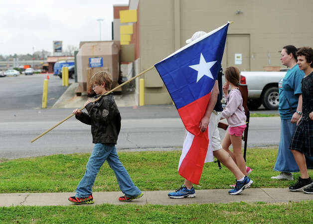 Ryley Franklin, 13, carries a Texas state flag during Saturday's rally. Come and Take It Beaumont held a march down Dowlen Road on Saturday. The participants carried long arms as well as Texas and United States flags from Sertinos Cafe to Lowes. Photo taken Saturday, 3/15/14 Jake Daniels/@JakeD_in_SETX Photo: Jake Daniels / ©2014 The Beaumont Enterprise/Jake Daniels
