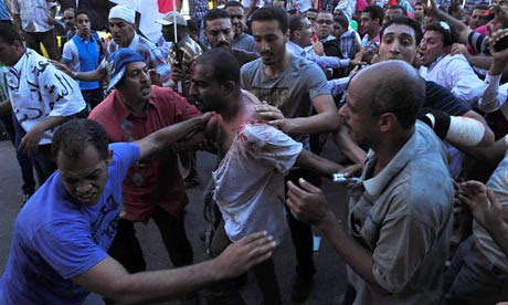 Egyptians help a wounded man after clashes in Alexandria. Political tensions escalated in late June 2013. by Pan-African News Wire File Photos