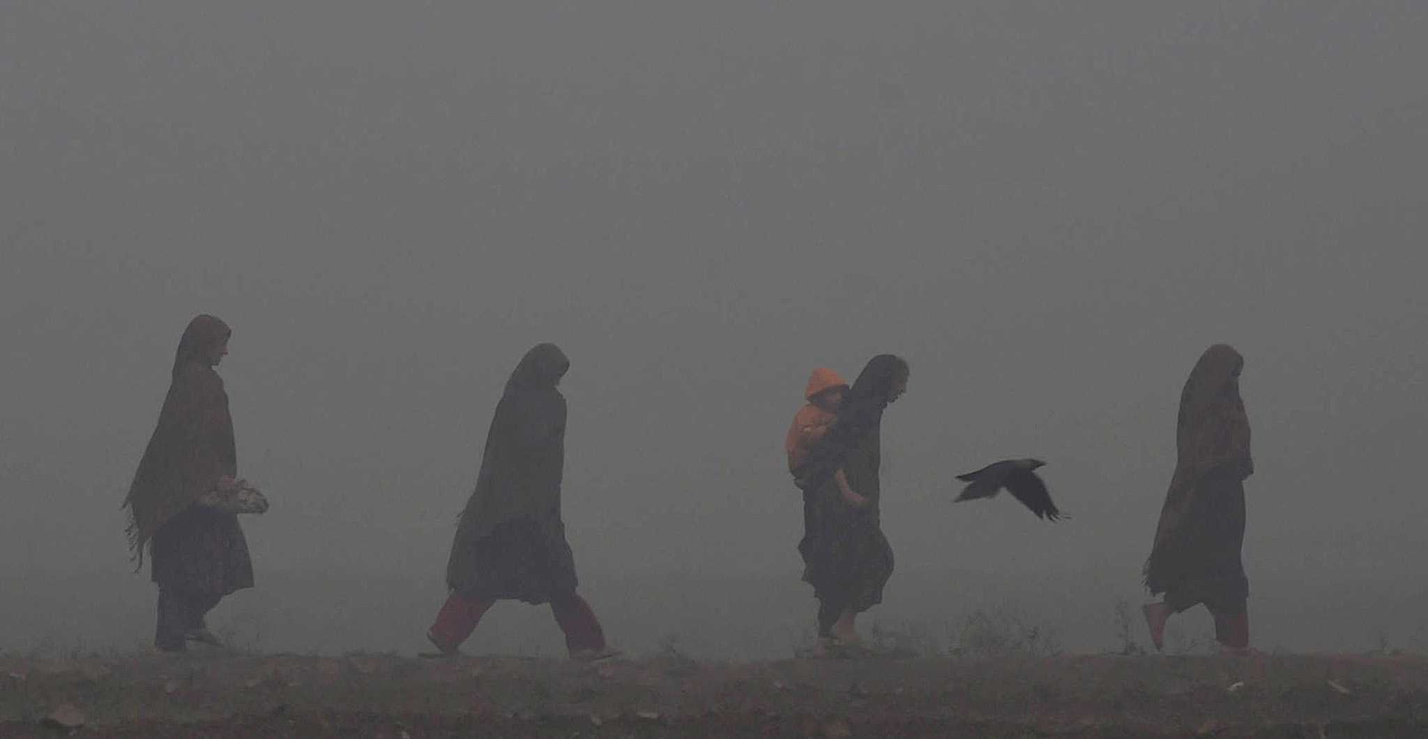 Pakistani women walk along a street on a foggy day in Lahore.