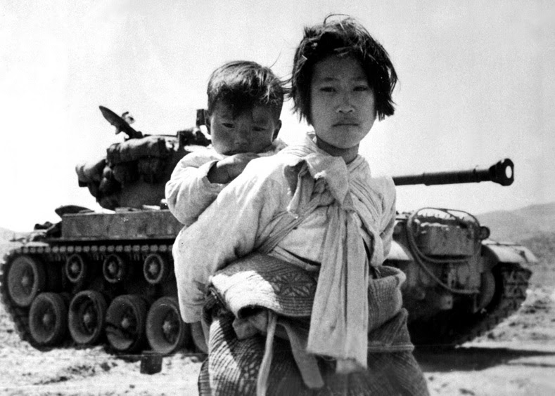With her brother on her back a war weary Korean girl tiredly trudges by a stalled M-26 tank, at Haengju, Korea. June 9, 1951.