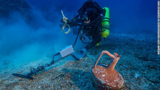 """After spending the last month at the historic wreck site, the <a href='http://www.whoi.edu/news-release/antikythera-finds' target='_blank'>Woods Hole Oceanographic Institute</a> (WHOI) announced that an international team of archaeologists had recovered new items from the Antikythera wreck. Pictured, Greek technical diver Alexandros Sotiriou discovers an intact """"lagynos"""" ceramic table jug and a bronze rigging ring. The new items have indicated the wreck site is much bigger than previously believed, scattered across 300 meters of seafloor."""