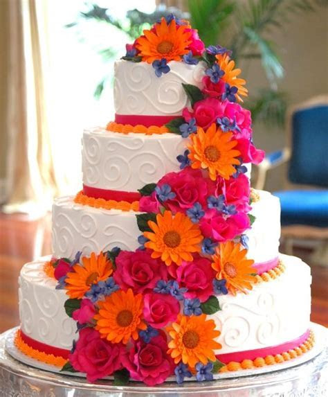 White wedding cake with orange, hot pink, and blue sugar