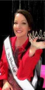 Marsha Schmid sitting while holding her crown and wearing her Ms. Wheelchair USA sash.