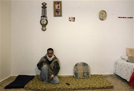 Egyptian immigrant Waleed Taleb sits inside his home in the island of Salamina near Athens November 28, 2012. REUTERS-John Kolesidis