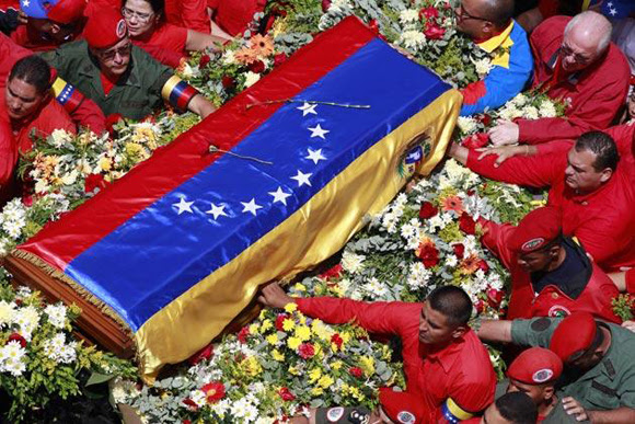 Varias personas sostienen el féretro que contiene el cuerpo de Hugo Chávez en el traslado del hospital donde falleció a la academia militar donde reposaría hasta su funeral en Caracas el 6 de marzo. Foto: Ricardo Mazalan/AP.