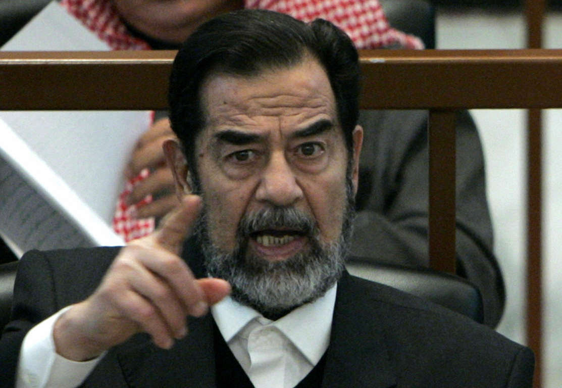 Baghdad, IRAQ:  Ousted Iraqi President Saddam Hussein reacts in court during the Anfal genocide trial in Baghdad, 21 December 2006.  The trial continued today with more documents presented by the prosecution regarding the 1980s Anfal campaign.      AFP PHOTO/POOL/NIKOLA SOLIC  (Photo credit should read NIKOLA SOLIC/AFP/Getty Images)