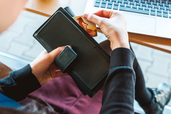 a person takes out a credit card from a wallet near a computer