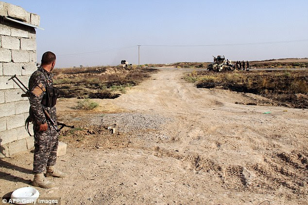 Iraqi security forces and Turkmen Shiite fighters, who volunteered to join the government forces, hold a position on August 4 in Amerli, some 100 miles north of Baghdad