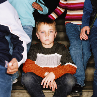 Small boy sitting on stairs as other children pass