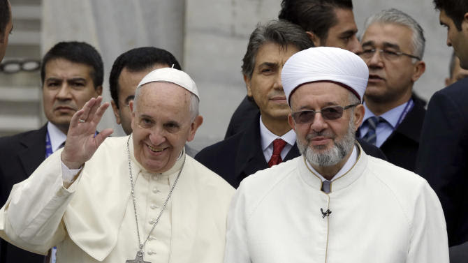 """Pope Francis waves to journalists as he stands by Istanbul Mufti Rahmi Yaran upon their arrival to the Blue Mosque in Istanbul, Turkey, Saturday, Nov. 29, 2014. Pope Francis visits two of Turkey's most iconic sites and shifts gears toward more religious affairs as he arrives in Istanbul for the second leg of his three-day visit to the Muslim nation. The Vatican says Francis will tour Istanbul's Sultan Ahmet mosque on Saturday and pause for a moment of """"reflection."""" (AP Photo/Thanassis Stavrakis)"""