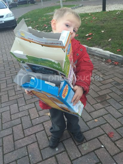 child holding cardboard boxes