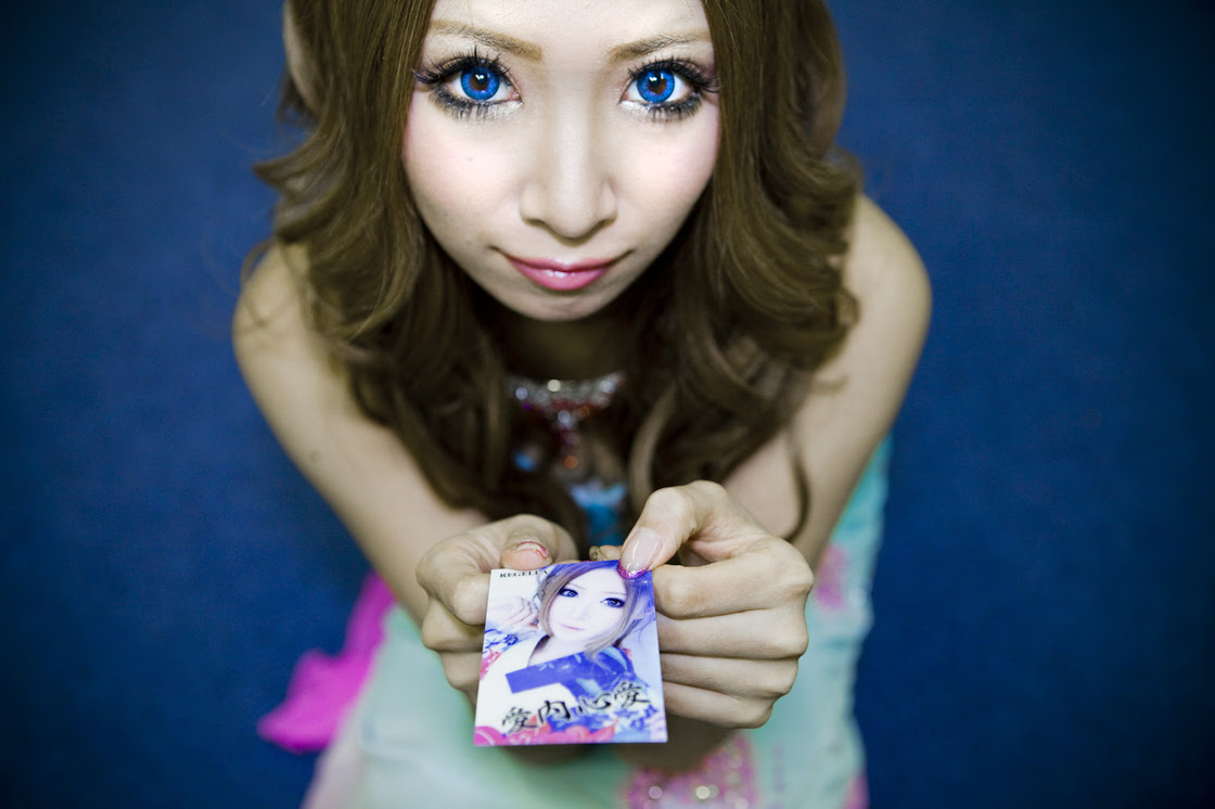 """Shiho Fukada's four-part photo series documents the effects of Japan's changing economy on both the young and the old. Here, Cocoa, 21, shows off her business card for her job as a """"hostess."""" Working as a hostess is a popular job for Japan's young women. But it comes with an expiration date — when they get too old, they are no longer wanted, leaving them with no skills and few options."""