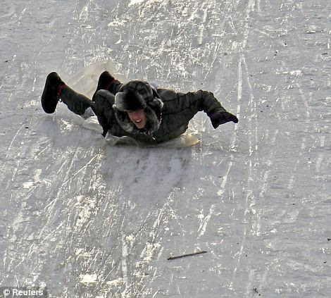 A boy uses a plastic sheet used to slide along a trail in the outskirts of Bucharest