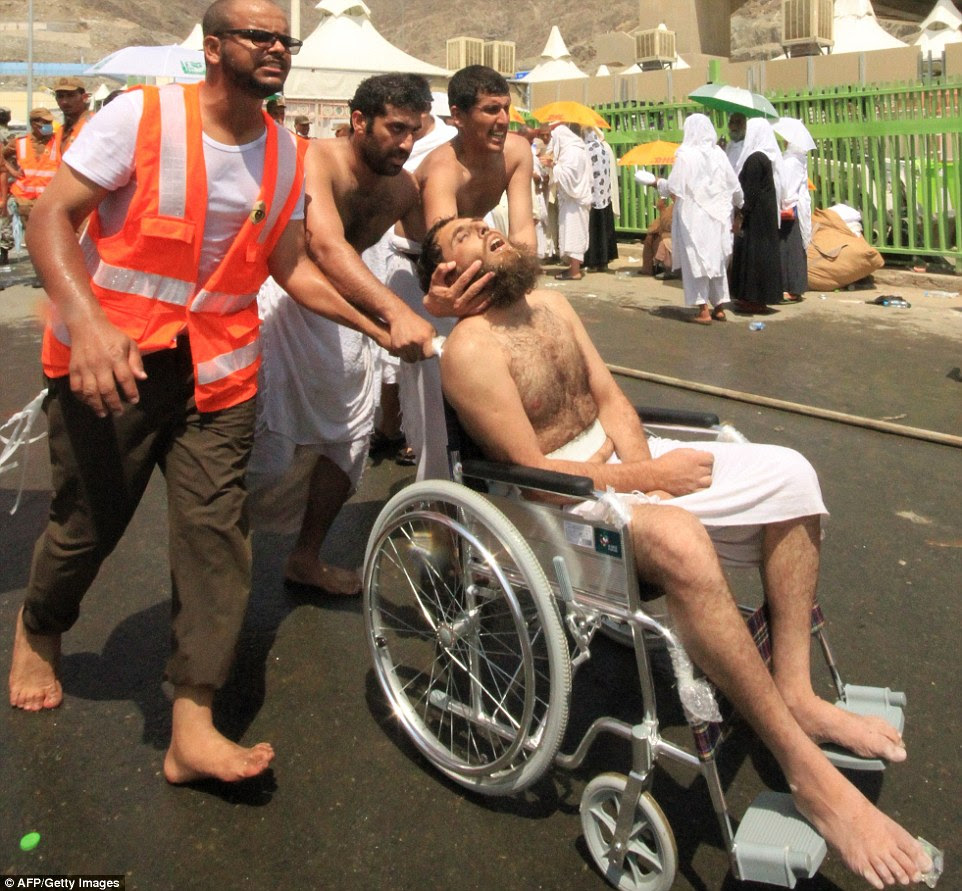 Saudi emergency personnel and Hajj pilgrims push a wounded person in a wheelchair at the site where hundreds were killed in a stampede