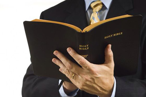 [Photo of a man holding an open Bible]