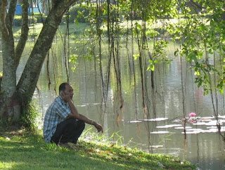 Man on the phone next to lake in Phuket Town