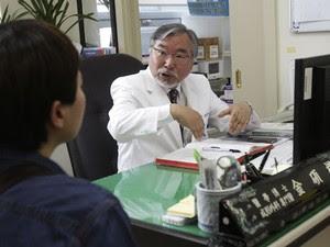 O cirurgião Kim Seok-Kwun com um paciente em seu consultório (Foto: Ahn Young-joon/AP)