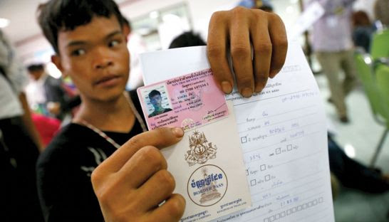 A Cambodian worker shows off his Thai employment permit.