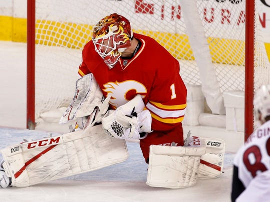 Calgary Flames' goalie Brian Elliott makes a save against Arizona Coyotes' Jamie McGinn during the first period of an NHL game in Calgary, Alberta, Saturday, Dec. 31, 2016. (Larry MacDougal/The Canadian Press via AP)