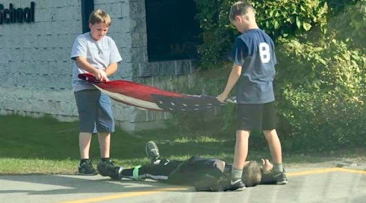 'Was waiting to pick up my kids from school when 3 boys took down the flag. They were having a hard time making sure it didn't touch the ground, when the third boy laid under it to honor it.'