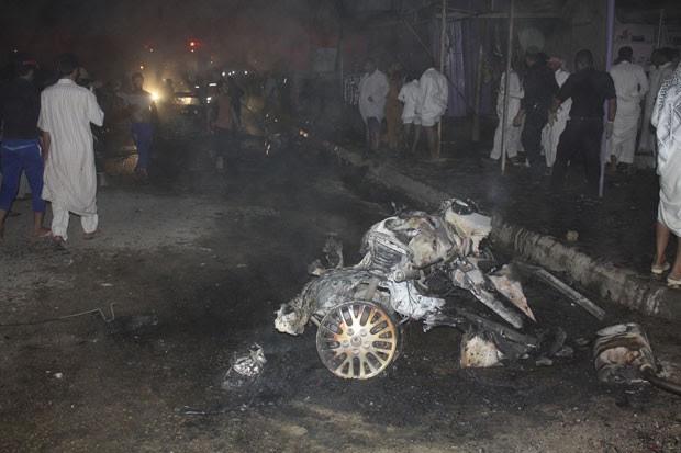 Pessoas passam ao redor dos destroços de um carro-bomba em Nasiriyah após explosão (Foto: Reuters/Stringer)