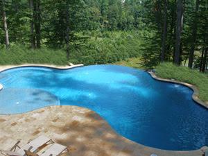 Beautiful Swimming Pool Designs with Travertine Pavers and Waterfall