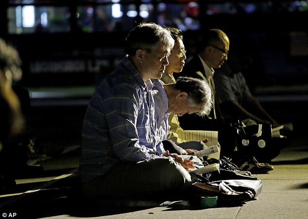 Hoping for change: People pray for peace on the Korean Peninsula near the U.S. Embassy in Seoul on Tuesday evening