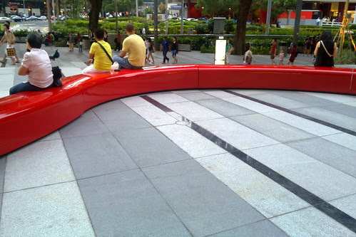 Long red curvy seat outside Ion