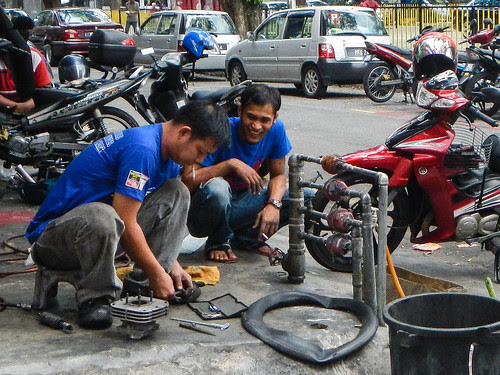 Motorcycle Mechanic on Sidewalk