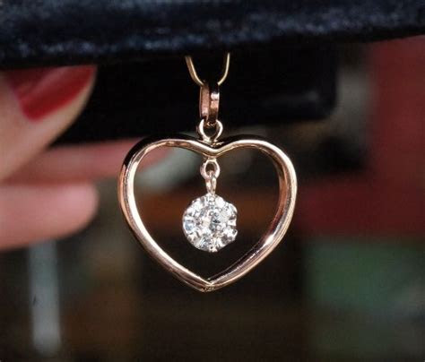 Old band shaped into heart with dangling diamond in an
