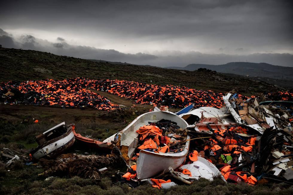 Botes dañados y miles de chalecos salvavidas usados por refugiados y migrantes durante su trayecto a través del mar Egeo, en Mithimna (Grecia)