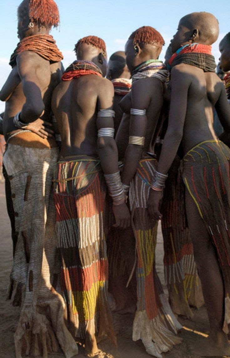 Africa | A group of Nyangatom girls and women with beautifully decorated leather skirts gather to dance.  Omo River valley, Southwest Ethiopia |  ©Nigel Pavitt