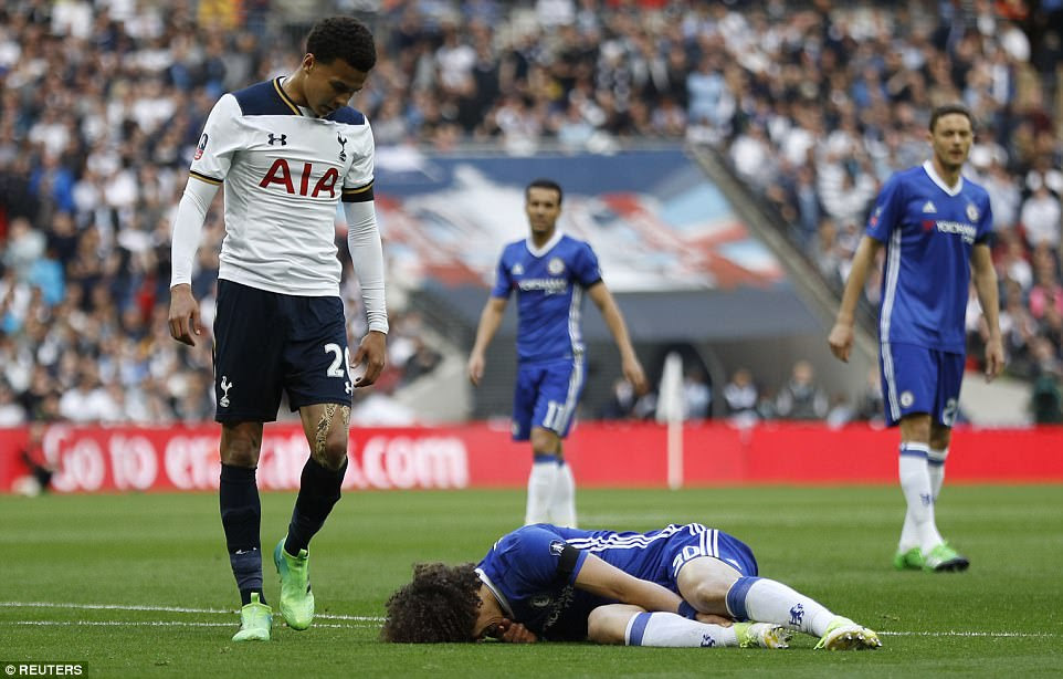 Alli glances down at the injured David Luiz after the pair clashed in the first-half of Saturday's match