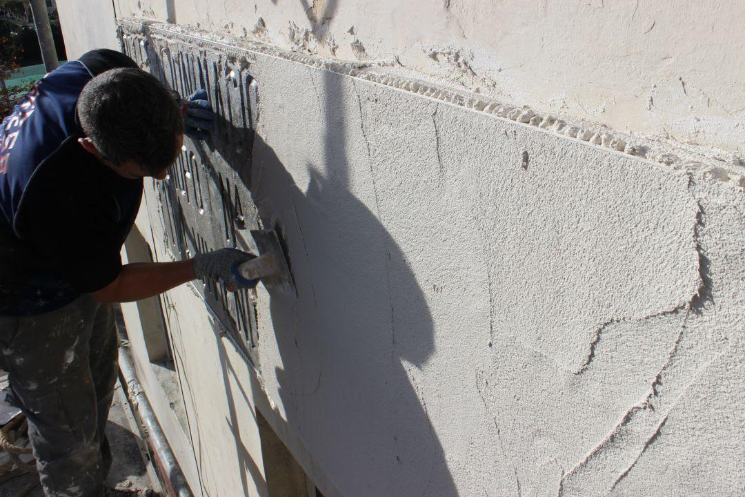 Trabajos de un operario para cubrir una placa con simbología franquista en un edificio de Irun.