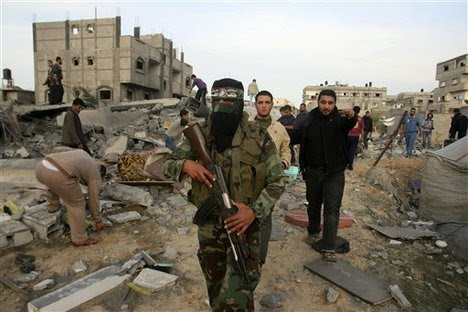 A Palestinian Hamas militant walks in the rubble of the destroyed house of Hamas militant Mohammad Abu Shmala, following an Israeli air strike in Rafah, southern Gaza Strip, Friday, Nov. 16, 2012.