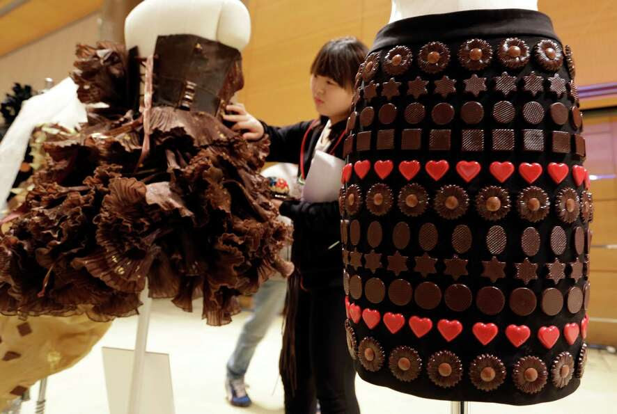 A woman checks the dresses partially made of chocolate before a chocolate fashion show in Seoul.