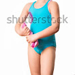 Swimmer: little 7 years old cute caucasian girlie in cyan swimming costume twistting a pink shammy, a chamois towel for divers. White background. Sport and ricreation concept