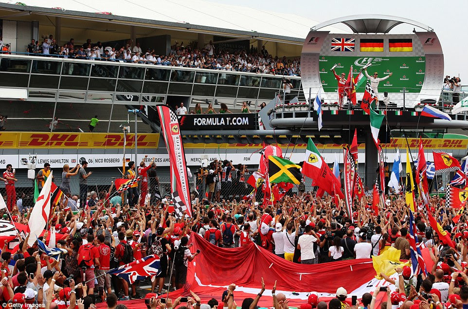 Rosberg celebrates on the podium in front of the Italian Grand Prix fans who packed the pit straight to watch the ceremony