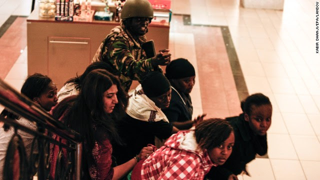 A soldier directs people up a stairway inside the Westgate shopping mall during a shootout in Nairobi, Kenya, on Saturday, September 21.