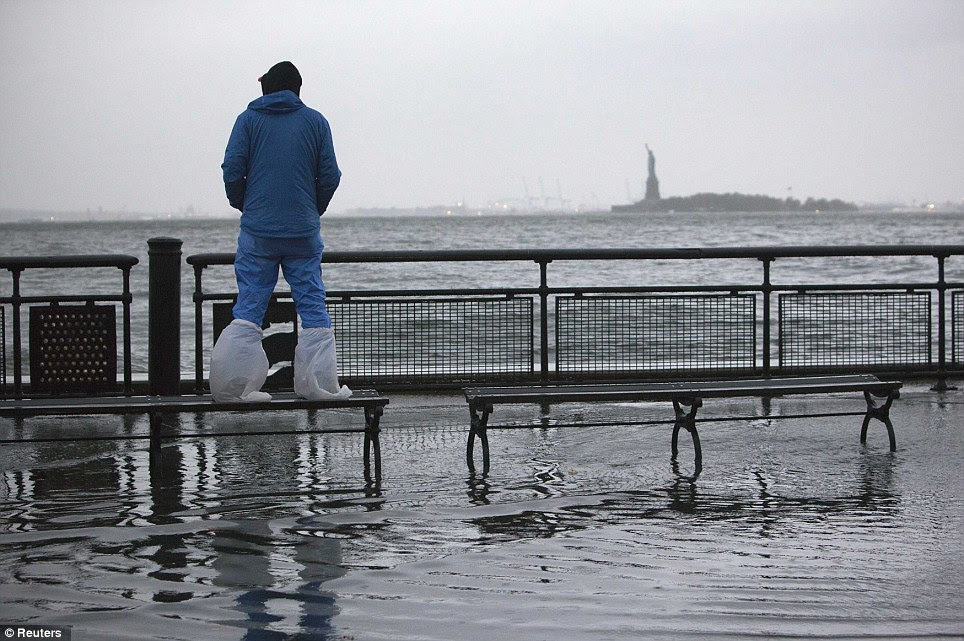 Watch out: A man looks at the rising tides in Battery Park as Hurricane Sandy makes its approach in Manhattan, New York, with the Statue of Liberty in the distance
