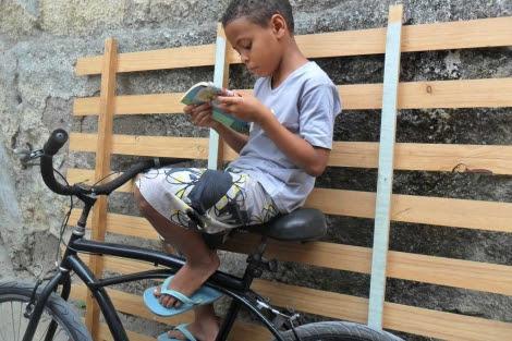Un niño de la favela leyendo un cuento.  Ediciones Ambulantes