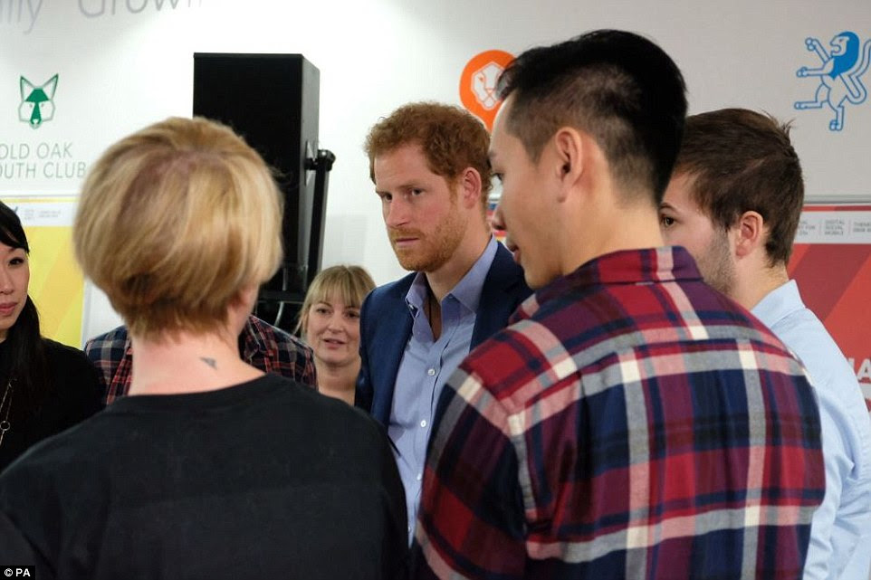 Prince Harry chats to volunteers and service users during a visit to the charity The Mix, which supports young people