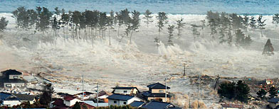 Houses are swept by water following a tsunami and earthquake in Natori City in northeastern Japan (Reuters/Kyodo)