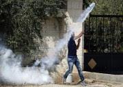 Un Palestinien relance en direction des soldats israéliens... (PHOTO NASSER SHIYOUKHI, AP) - image 3.1