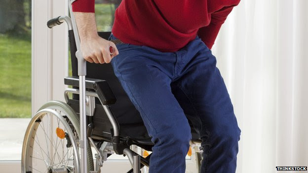 A man using a crutch and getting up out of his wheelchair